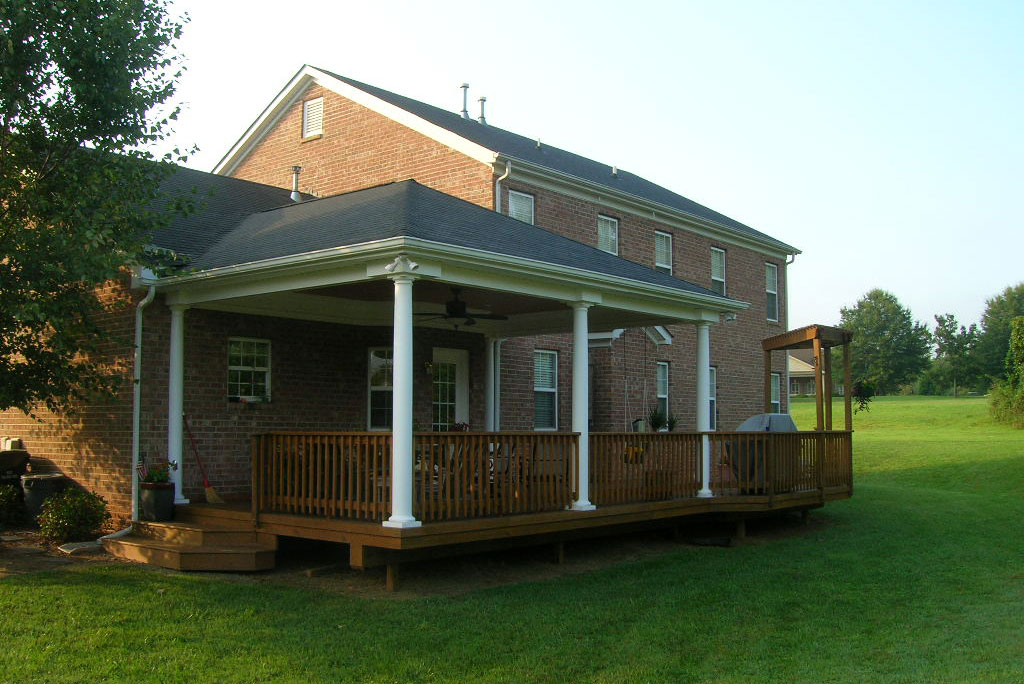 back porch with white columns and green lawn